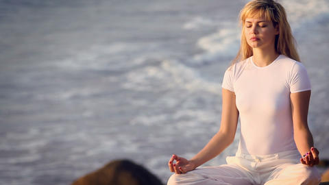 Young Woman Practising Yoga on the beach Footage