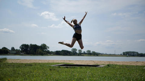 Active joyful blonde girl jumping on a trampoline in nature in slow motion Live Action