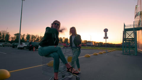 Two millennials girlfriends in street clothes have fun in a supermarket parking Footage
