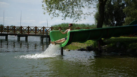 Young red-haired guy slides off a water slide into a lake in slow motion Live Action