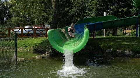 Happy blonde girl slides off a water slide into a lake in slow motion Live Action
