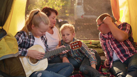 Tourist family singing song by guitar in camping tent in forest hike. Friendly Live Action