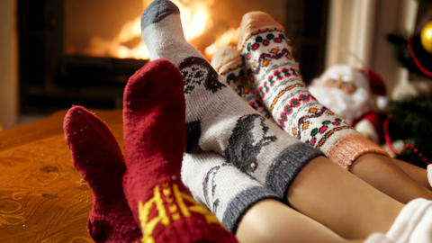 Closeup 4k footage of three pairs of feet wearing warm woolen socks warming in Live Action