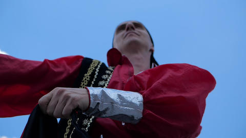 A toreador in ethnic costume waves red cloth against the blue sky, slow motion Footage