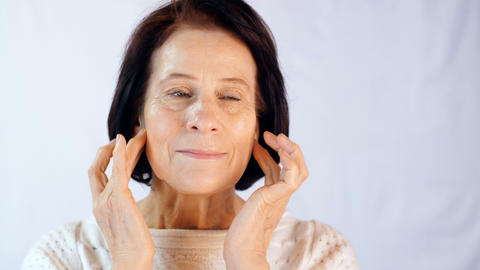 Adult woman applying cream on face Footage