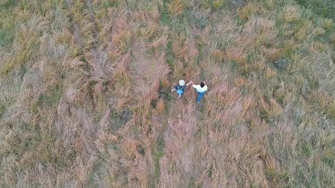 guy with a girl walking through a field Live Action