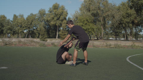 Soccer player helping teammate to get up after foul Live Action