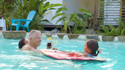 Adult Couple Enjoying The Pool With Their Granddaughter Live Action