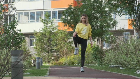 Young sporty woman exercises in an urban environment Footage
