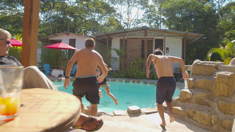 Tourists Enjoying Drinks Are Thrown Into A Pool At A Lodge Live Action
