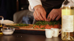 The cook sprinkles finely chopped herbs with a large piece of raw salmon fillet Live Action