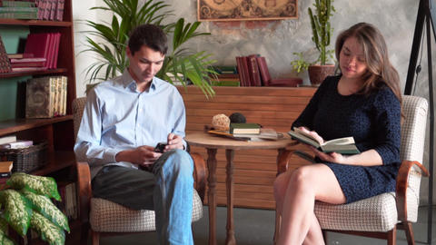 The guy and the girl are sitting in the home library. The guy looks into the Live Action