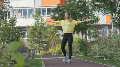 Young sporty woman exercises in an urban environment Live Action