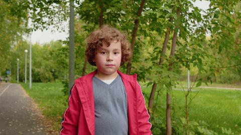 Young curly boy walking on road in summer park. Portrait teenager boy walking in Live Action