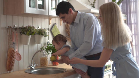 Dad holds her daughter in her arms and brings to the sink, daughter holds a Live Action