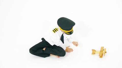 Boy in pilot's uniform lands generic wooden toy plane Live Action
