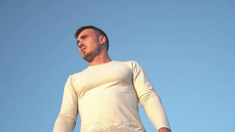 Portrait of a young guy on a background of blue sky. Close-up of a guy wearing a Live Action