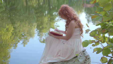 Redhead attractive caucasian girl reading the book in dark red cover on the bank Live Action