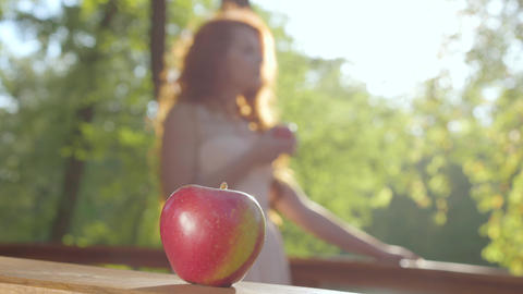 Close-up of a red apple with a redhead caucasian woman in the sunshine at the Live Action
