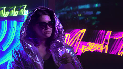 Millennial cool modern pretty girl smoking cigarette near glowing neon wall at Footage