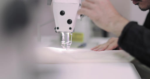 Closeup of hands stitching with an industrial sewing machine Footage