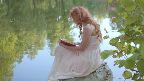 Side view of the redhead attractive caucasian girl reading the book in dark red Live Action