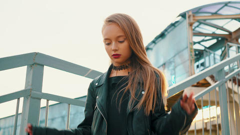 Rock girl in black leather jacket walking down stairs on golden sunlight Footage