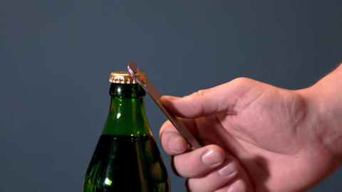 Man opens bottle with fizzy drink with a special opener. Glass bottle with metal Live Action