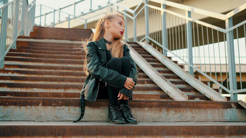 Rock girl in black leather jacket sitting on stairs. Young girl in black leather Live Action