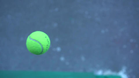 Video of a tennis ball flying. The main object of the ball is out of focus Footage