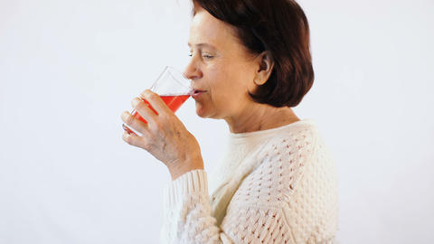 Woman drinking red juice on white background Footage