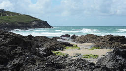 Waves rolling into a rocky cove, with coastal path in distance Footage