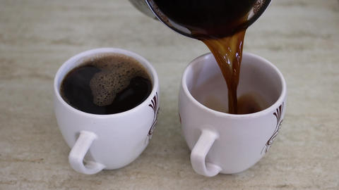 Pouring black coffee in two white cups Live Action