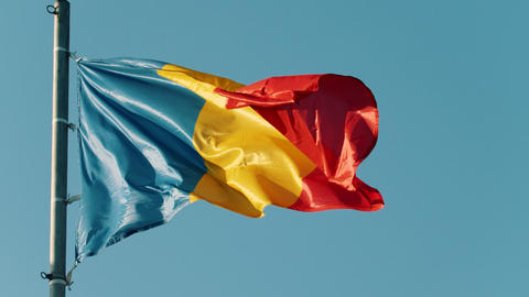 Flag of Romania blowing in the wind on the background of clear blue sky Footage