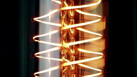 close-up of retro vintage light bulb with old technology with filament built-in with warm light Footage