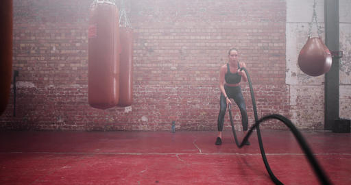 Young adult female working out with battle ropes Live Action