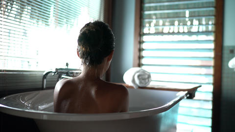 bath woman relaxing in hot bathtub in Luxury hotel resort suite room pampering Live Action