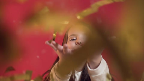 Slow motion of adorable cheerful little girl with braces blowing golden confetti Footage