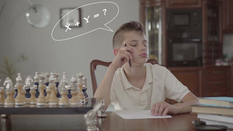 Pensive schoolboy doing homework sitting at a table at home Live Action