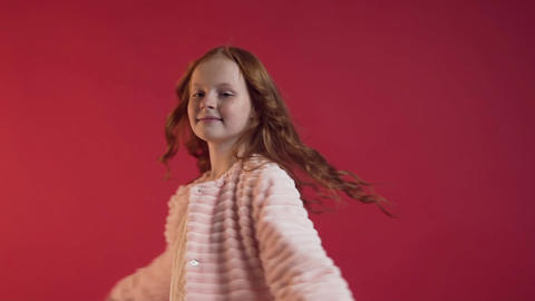 Attractive happy teen girl with red hair turning around and smiling near the red Footage