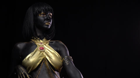 Model with black and gold body art and makeup is sitting, black background, 4k Live Action