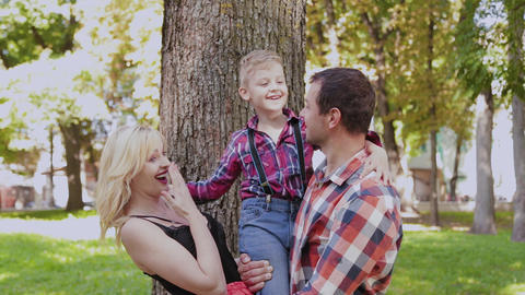 Happy cheerful family hugging and smiling by the tree in the park Live Action