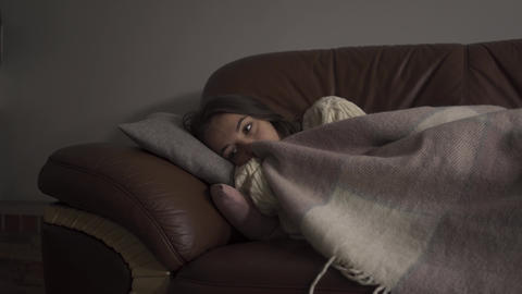 Sick young woman with dark circles under her eyes lying under blanket at home Live Action