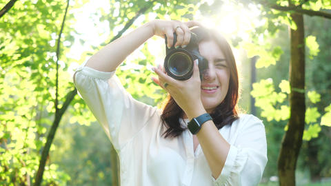 Pretty smiling girl photographer in white shirt is making photos in a park on a Footage