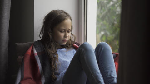 Sick caucasian girl covered in blanket sitting on windowsill at home. The child Live Action