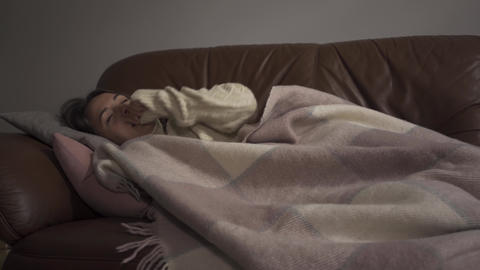Sick young caucasian girl lying under blanket at home. The woman has fever Live Action