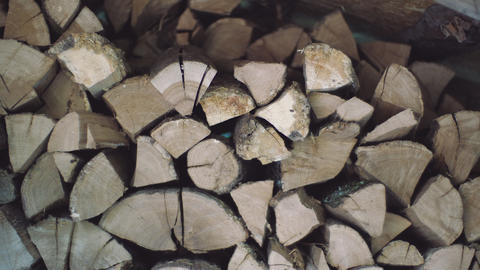 Man puts chopped wood pieces neatly onto one each other in a pile. Stacked wood Footage