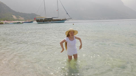 Adorable happy child wide-brimmed hat standing in sea water and dancing Live Action