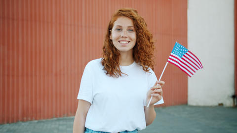 Teenage girl patriot holding US flag outdoors smiling looking at camera Live Action