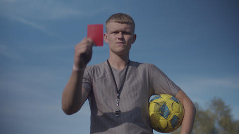 Soccer referee with red card sending off player Live Action
